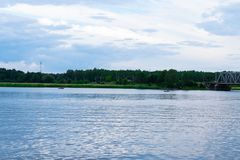 Summer landscape with river and clouds on blue sky. Fishermen in their boat stock photography
