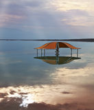 The picturesque gazebo for swimmers. Incredible optical effects at the Dead Sea. The picturesque gazebo for swimmers is reflected in a smooth sea surface Stock Photo