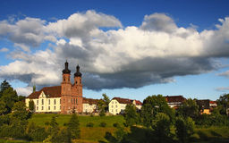 Picturesque German town with a church at sunset. Picturesque brown Roman church on green hills Stock Photo