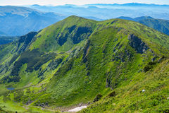 Picturesque green ridge against the background of mountains Royalty Free Stock Images