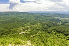 Picturesque hilly valley overgrown with dense forest and shrubs, with a country road passing through it. Bird`s eye view. View of the beautiful hilly valley royalty free stock photos