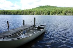Canoe Moored at Lake Dock. A picturesque image of a steel Canoe with two oars moored on a Vermont mountain lake of a wilderness retreat ready to be taken out for Royalty Free Stock Image