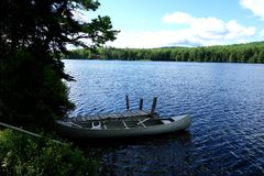 Side View of a Canoe Moored at Lake Dock. A picturesque image of a steel Canoe with two oars moored on a Vermont mountain lake of a wilderness retreat ready to Stock Photos