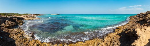 Beach Punta della Suina, Salento, Italy. Picturesque Ionian sea beach Punta della Suina, Salento, Puglia, Italy. Gallii town view in far. People are royalty free stock photography