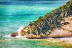 Picturesque islets Faraglioni di Puglia in summer Adriatic sea bay Baia Delle Zagare. Mattinata Faraglioni stacks and beach coast of Mergoli, Vieste Gargano royalty free stock image