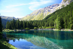 Picturesque lake and alps. Alpine mountains and forest reflected on lake in Tirol, Austria Stock Images