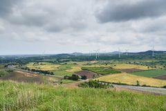 Picturesque Landscape of farm field with wind generator. View from Yongnuni Oreum Yonganak, a parasitic volcano in Jongdal-ri, Jeju, Korea Royalty Free Stock Photos