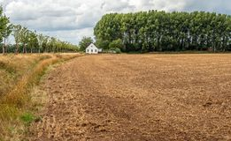 Picturesque landscape with a large field after harvesting. Landscape with a large field after harvesting. In the background is a white plastered house and a long royalty free stock photos