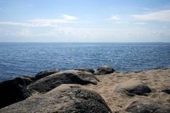 Picturesque landscape with sandy shore, boulders, sea and sky. Atmospheric view stock image