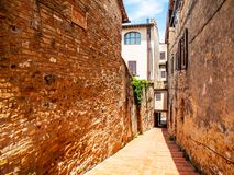 Picturesque medieval narrow street of San Gimignano old town, Tuscany, Italy Stock Photos