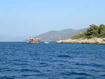 Ship with tourists near the rocky green island in the sea Royalty Free Stock Image