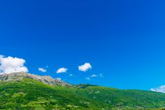 A picturesque mountain peak against a blue sky. With white clouds Stock Photos