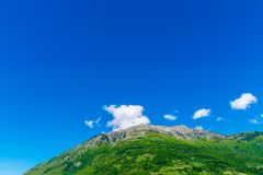 A picturesque mountain peak against a blue sky. With white clouds Royalty Free Stock Photography