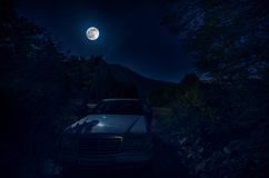 Picturesque night landscape of deep blue sky with bright moon lighting over car and trees. Picturesque night landscape of deep blue sky with bright moon lighting Stock Image