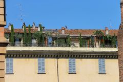 Picturesque old building with trees on terrace Stock Image