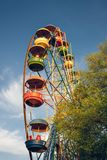 Picturesque old Ferris wheel against a clear blue sky. Children`s holiday Royalty Free Stock Photos
