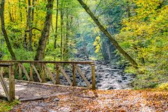 Picturesque old iron bridge over a forest stream. In the Caucasus mountains in a sunny autumn day, Georgia royalty free stock image