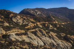 Calabasas Peak Trail. Picturesque overlook of Calabasas Peak Trail winding through the canyon with rock formations on a sunny day with blue sky and clouds Stock Photos