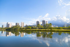 The picturesque panorama of Waikiki suburbs framed by the mirror-like canal surface, green golf course and distant mountains. Stock Photo