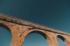 The picturesque part of the historic aqueduct in Spain against the blue sky stock images