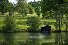 Picturesque pastures with sheep and lake with old boat house, Scotland, UK Stock Image