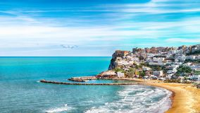 Picturesque Peschici with wide sandy beach in Puglia, adriatic coast of Italy. Location Peschici, Gargano peninsula, Apulia, southern Italy, Europe royalty free stock photography