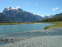 Picturesque Picnic Spot. Crisp blue river leading to a snow capped Mountain range in Fiordland National Park on the road to Stock Photos
