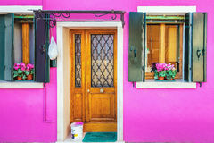 Picturesque pink wall. Picturesque entrance door,windows with green shutters and paint basket on pink wall of houses on the famous island Burano, Venice, Italy Stock Photos