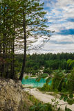 A picturesque place of azure pond and coniferous trees. A beautiful view of the azure quarry formed at the site of the kaolin quarry Stock Image