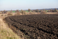Picturesque plowed field on the turn. Edge of field after plowing in autumn Stock Photography