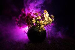 Picturesque purple spring flowers in glass vase standing in a row on a dark background with stars with light and fog. Flower conce. Pt. Dark decoration Stock Photo