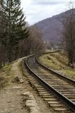 Picturesque railway track disappearing behind the horizon. Against the backdrop of the picturesque Carpathian Mountains Stock Image