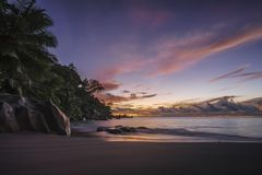 Picturesque red sky after sunset on paradise Beach on the seyche. Beautiful romantic red sky after the sunset on paradise beach on the seychelles with granite Stock Photos