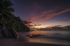 Picturesque red sky after sunset on paradise Beach on the seyche. Beautiful romantic red sky after the sunset on paradise beach on the seychelles with granite Royalty Free Stock Images