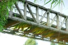 Picturesque reflection of a bridge in vibrating water surface. Picturesque reflection of a bridge in vibrating water surface with green grass royalty free stock photography