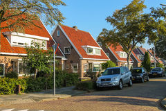 Picturesque residential houses and parked autos in small Dutch t Royalty Free Stock Photo