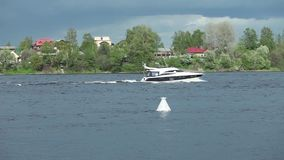 Picturesque river landscape with a floating yacht. Dramatic sky reflected in the water stock video footage