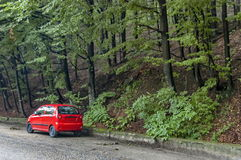 Picturesque road with red car at Balkan mountain in rainy day. Petrohan, Bulgaria Royalty Free Stock Image