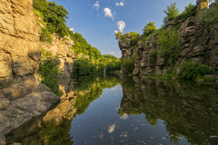 Picturesque rocks reflected in water in river canyon. At sunny summer day Royalty Free Stock Photography