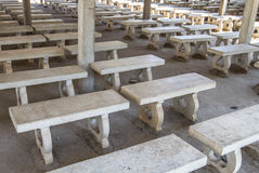 Picturesque rows of white stone benches perfectly aligned. With nobody Stock Images