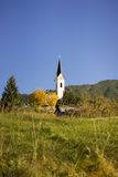 Picturesque rural church in the Tirol. Austria with its spire rising above colorful autumn trees in a scenic alpine landscape stock photo