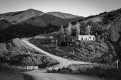 Picturesque rural house on a hill and rural road, Mahia Peninsula, New Zealand. Black and white, horizontal image of picturesque rural road and house on a hill stock photography