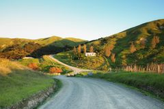 Picturesque rural house on a hill and rural road, Mahia Peninsula, New Zealand. Colour, horizontal image of picturesque rural road and house on a hill bathed in stock images