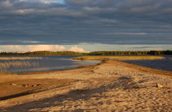 Picturesque sandy spit on forest lake. Royalty Free Stock Image