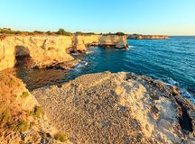 Surise Faraglioni at Torre Sant Andrea, Italy. Picturesque seascape with cliffs, rocky arch and stacks faraglioni, at Torre Sant Andrea in morning sunlight Stock Image
