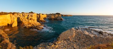 Surise Faraglioni at Torre Sant Andrea, Italy. Picturesque seascape with cliffs, rocky arch and stacks faraglioni, at Torre Sant Andrea in morning sunlight Royalty Free Stock Photos