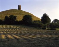 Picturesque Somerset - Glastonbury Tor. Evening sunshine hay field, Glastonbury Tor, Somerset, UK Royalty Free Stock Image