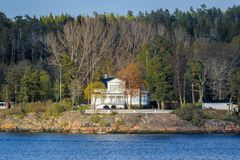 Picturesque spring coastal landscape of Stockholm archipelago with luxury waterfront villa named Elvira surrounded by bare trees. STOCKHOLM, SWEDEN - May 03 stock photo