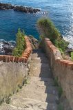 Picturesque staircase at the end of a path that reaches the sea in Riomaggiore, 5 terre. Liguria, Italy stock photos