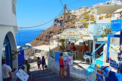 Picturesque commercial street Fira Santorini Greece. Picturesque steep narrow street lined up with typical white cave houses with cozy restaurants ending at Royalty Free Stock Image